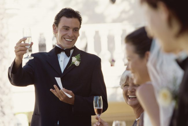 Best man making a toast on the head table at a wedding reception