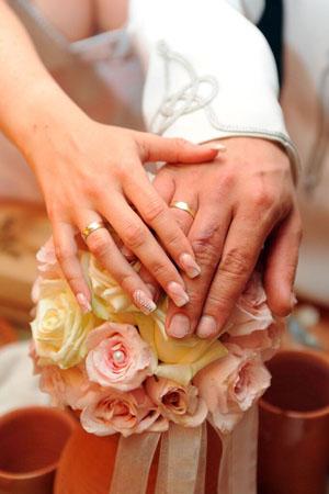 az_ifjú_pár_gyűrűs_kezei_összeérnek_az_esküvői_csokron