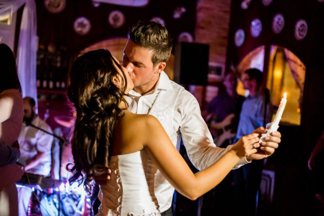 Az ifjú pár az esküvő utáni partyn csókolózik.