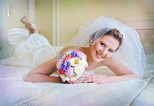 Boldog menyasszny az ágyon, virágcsokorral a kezében