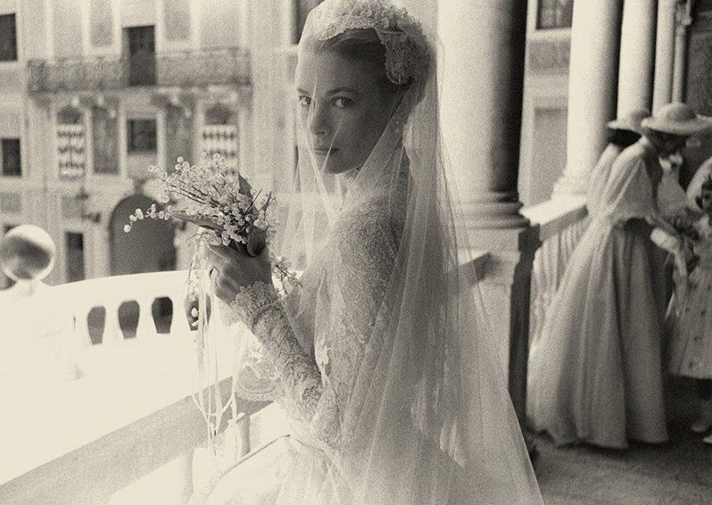Grace Kelly esküvői ruhában az árkádok alatt, menyasszonyi csokorral a kezében