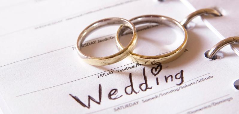 Esküvői gyűrűk egymáson egy naptáron, melybe fel lett jegyezve a házasságkötés napja